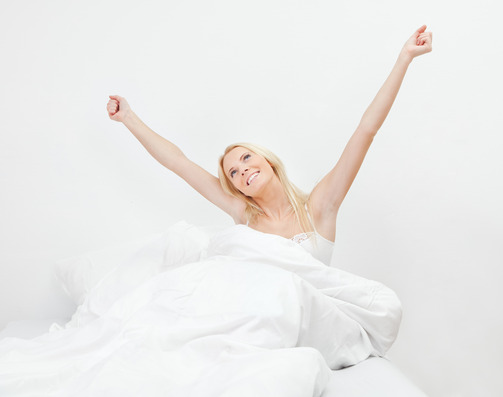 Young happy smiling woman waking up