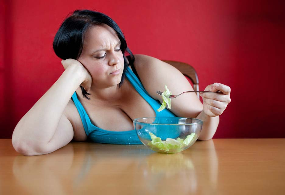 Unhappy overweight woman with her meal, a bowl with a few leaves