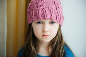 Adorable sad child girl in pink knitted hat