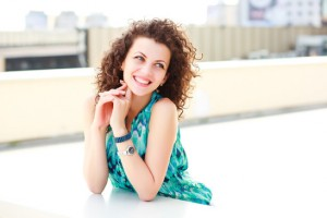 beautiful women with curly hair smiling outdoor on a sunny day