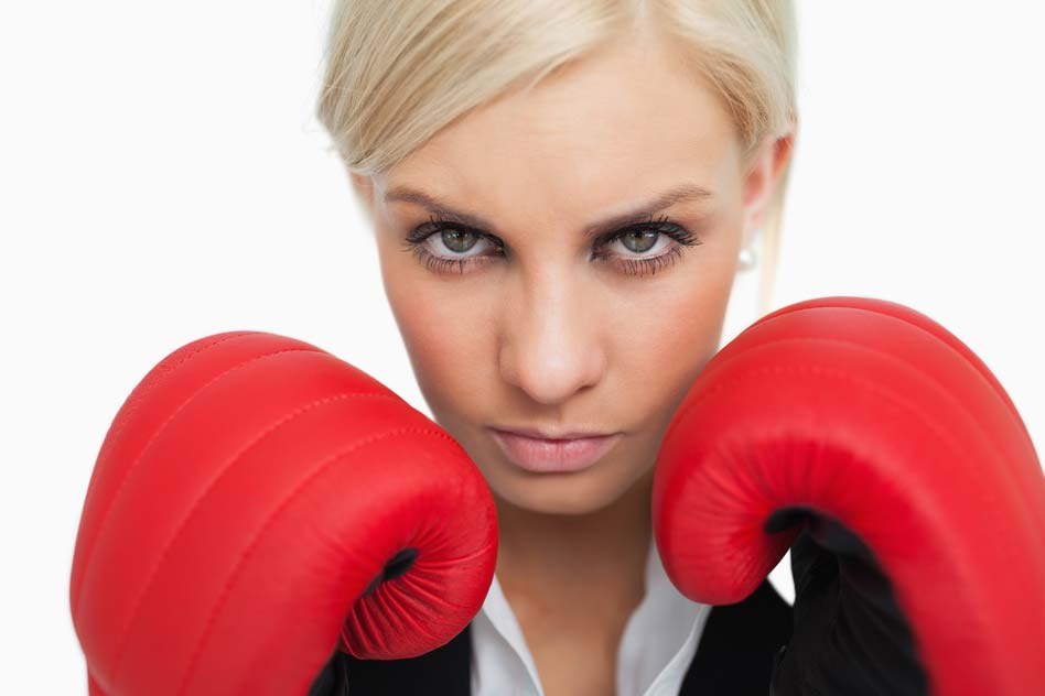 Serious green eyed woman with red gloves fighting against white background